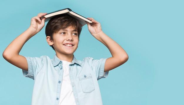 Jovem garoto segurando o livro na cabeça