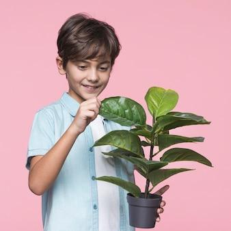 Jovem garoto segurando o vaso de flores
