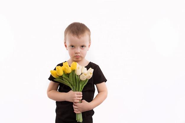 Jovem garoto segurando tulipas isoladas no branco