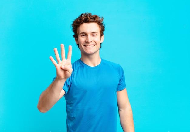 Jovem garoto sorrindo e parecendo amigável, mostrando o número quatro ou o quarto com a mão para a frente, em contagem regressiva