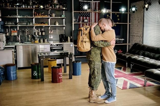 Jovem gay chateado se despedindo de seu namorado para o exército na cozinha de seu apartamento