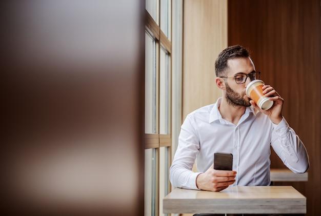 Jovem geeky elegantemente vestido sentado no refeitório ao lado da janela, bebendo café em um copo descartável e usando o telefone inteligente para verificar as mensagens nas redes sociais.