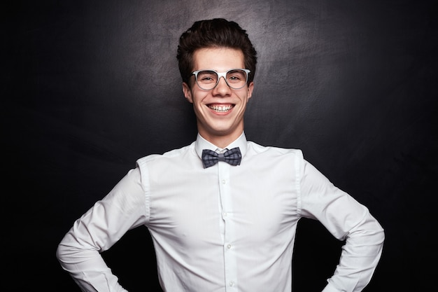 Jovem gênio do sexo masculino com óculos, camisa formal branca e gravata borboleta, sorrindo alegremente e olhando com confiança enquanto está de pé contra o quadro-negro