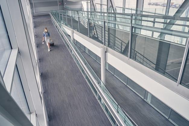Jovem gentil atravessando paredes de vidro durante o embarque na aeronave