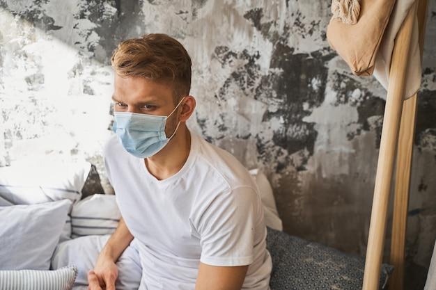 Jovem gentil, imerso em pensamentos, usando máscara médica estéril enquanto segue regras de isolamento