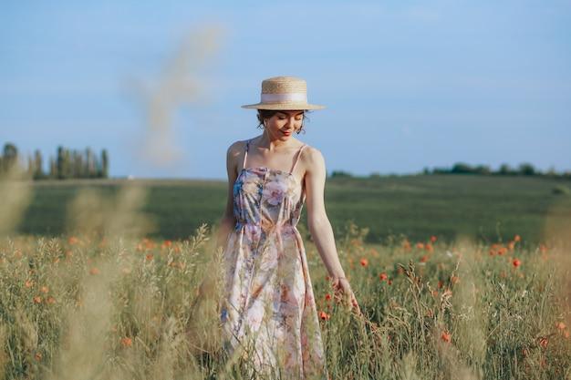 Jovem gentil relaxante no feixe de luz do sol. retrato de corpo inteiro em campo de flores