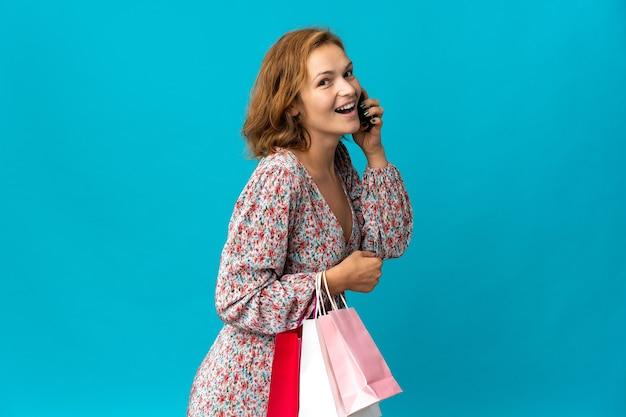 Jovem georgiana com uma sacola de compras isolada na parede azul, segurando sacolas de compras e ligando para um amigo com o celular