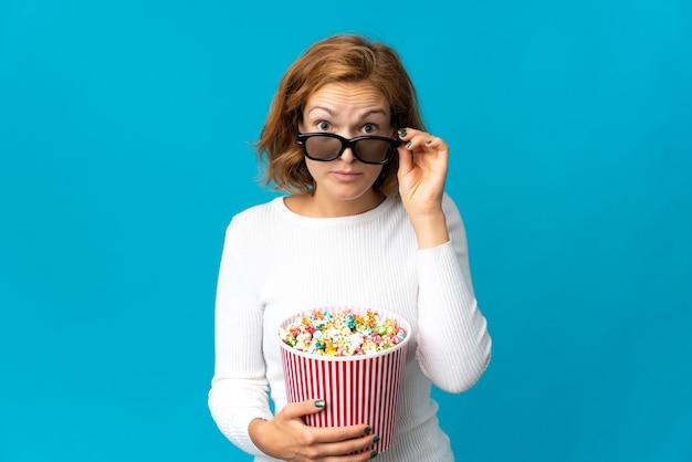 Jovem georgiana isolada em um fundo azul surpresa com óculos 3d e segurando um grande balde de pipocas