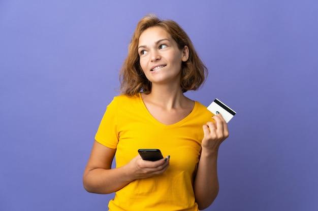 Jovem georgiana isolada em um fundo roxo, comprando com o celular com um cartão de crédito enquanto pensa