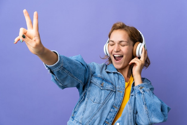Jovem georgiana isolada em um fundo roxo ouvindo música e cantando