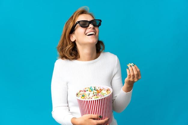 Jovem georgiana isolada em uma parede azul com óculos 3d e segurando um grande balde de pipocas