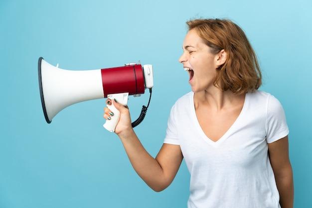 Jovem georgiana isolada em uma parede azul gritando em um megafone para anunciar algo em posição lateral