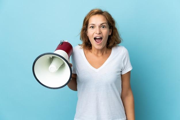 Jovem georgiana isolada na parede azul segurando um megafone e com expressão de surpresa