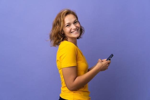Jovem georgiana isolada na parede roxa enviando uma mensagem ou e-mail com o celular
