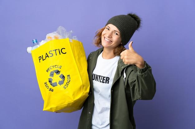 Jovem georgiana segurando um saco cheio de garrafas de plástico para reciclar com o polegar para cima porque algo bom aconteceu