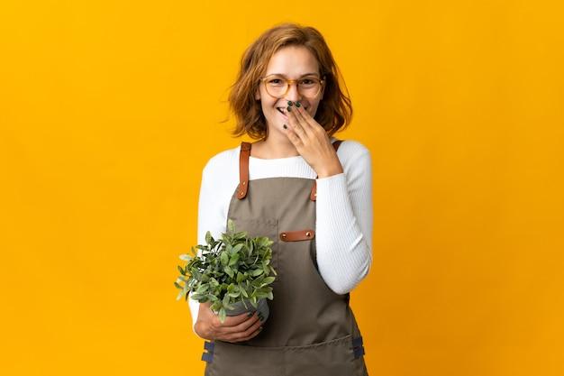 Jovem georgiana segurando uma planta isolada