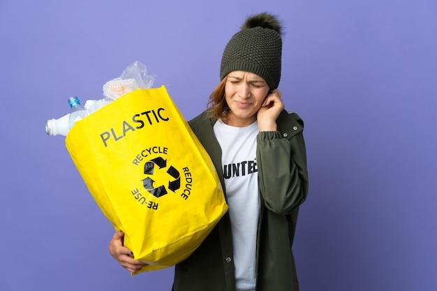 Jovem georgiana segurando uma sacola cheia de garrafas de plástico para reciclar frustrada e cobrindo as orelhas