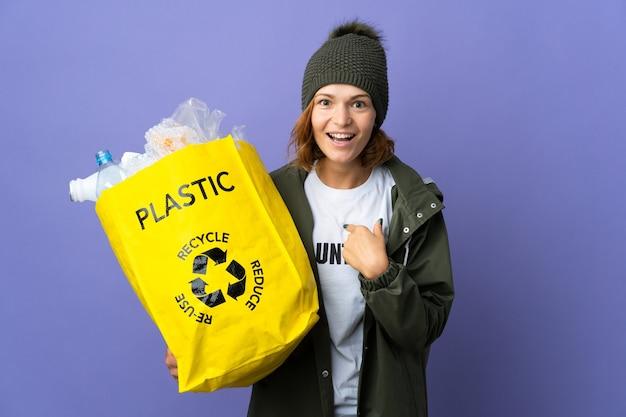 Jovem georgiana segurando uma sacola cheia de garrafas plásticas para reciclar com expressão facial surpresa
