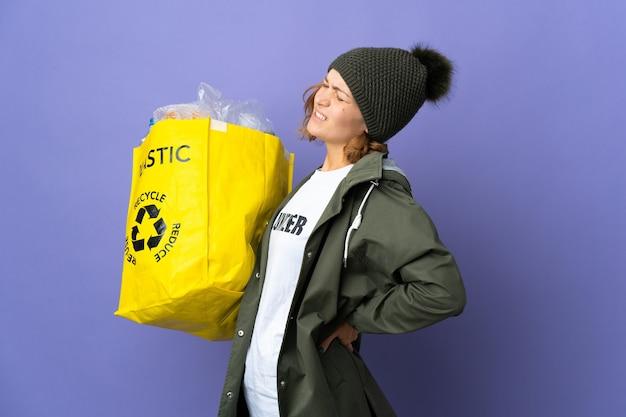 Jovem georgiana segurando uma sacola cheia de garrafas plásticas para reciclar sofrendo de dor nas costas por ter feito um esforço