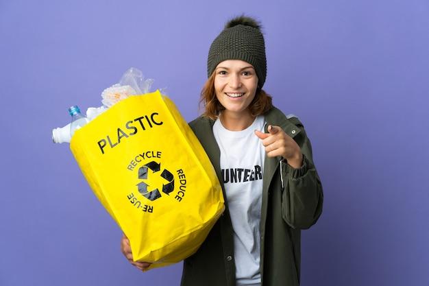 Jovem georgiana segurando uma sacola cheia de garrafas plásticas para reciclar surpresa e apontando para a frente