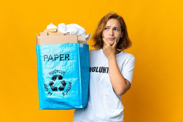 Jovem georgiana segurando uma sacola cheia de papel para reciclar, tendo dúvidas