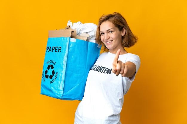 Jovem georgiana segurando uma sacola de reciclagem cheia de papel para reciclar, mostrando e levantando um dedo
