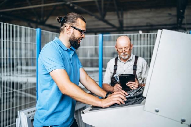 Jovem gerente com barba, mostrando e inspecionando o processo de trabalho do trabalhador profissional adulto na grande fábrica.