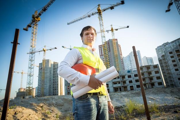 Jovem gerente de construção posando em um canteiro de obras em um dia ensolarado