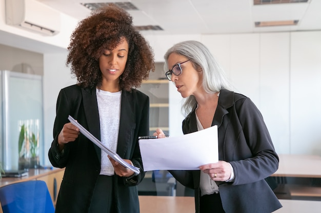 Jovem gerente de conteúdo mostrando o documento para um colega adulto. duas colegas femininas muito contentes segurando papéis e em pé na sala do escritório. conceito de trabalho em equipe, negócios e gestão