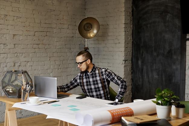 Jovem gerente de criação de uma empresa de arquitetos, tendo uma conversa online matinal