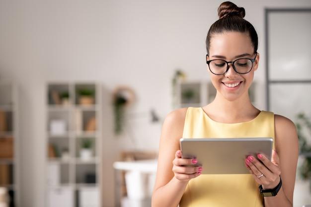 Jovem gerente de projeto sorridente em óculos usando tablet digital enquanto trabalha com plataformas online