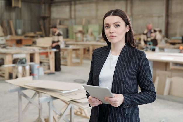 Jovem gerente de vendas sério de uma fábrica de móveis usando o touchpad enquanto fica de pé contra o interior da oficina e trabalhadores do sexo masculino