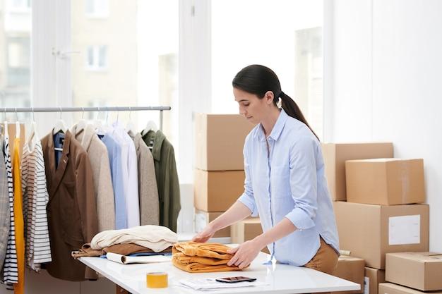 Jovem gerente dobrando um dos itens da nova coleção casual de moda casual enquanto o prepara para embalar