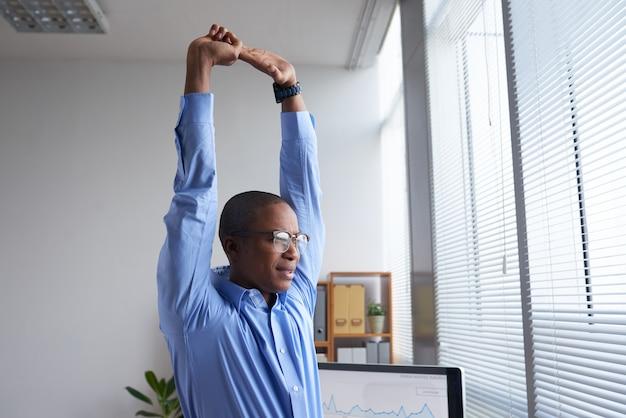 Jovem gerente fazendo um bom alongamento antes do trabalho, olhando para a janela
