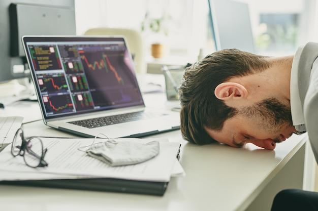 Jovem gerente frustrado batendo a cabeça na mesa após análise financeira do orçamento da empresa