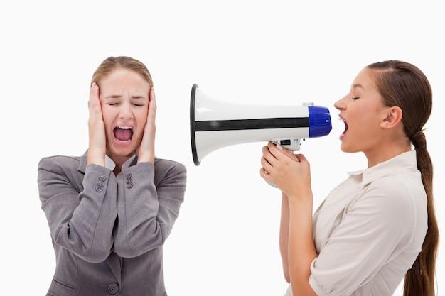 Jovem gerente gritando com seu empregado através de um megafone