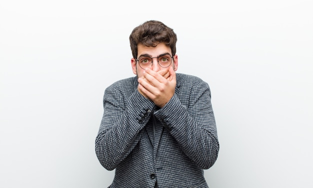 Jovem gerente homem cobrindo a boca com as mãos com uma expressão chocada e surpresa, mantendo um segredo ou dizendo oops contra parede branca