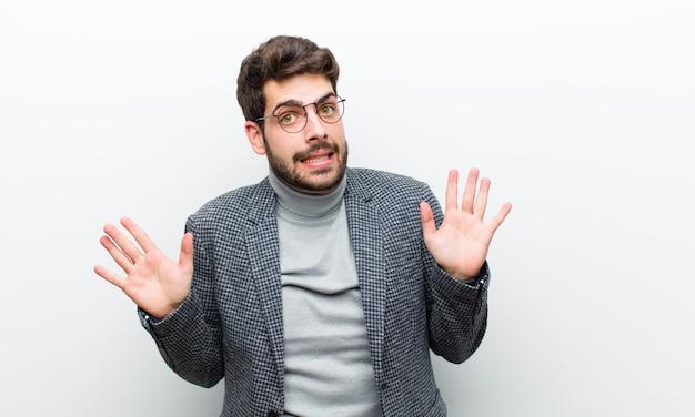 Jovem gerente homem olhando nervoso, ansioso e preocupado, dizendo que não é minha culpa ou eu não fiz isso contra uma parede branca