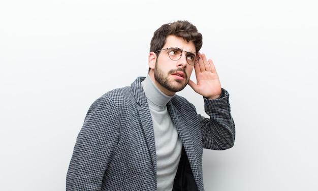 Jovem gerente homem olhando sério e curioso, ouvindo, tentando ouvir uma conversa secreta ou fofoca, bisbilhotando contra parede branca