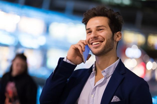 Jovem gerente no telefone ao ar livre em um ambiente urbano à noite