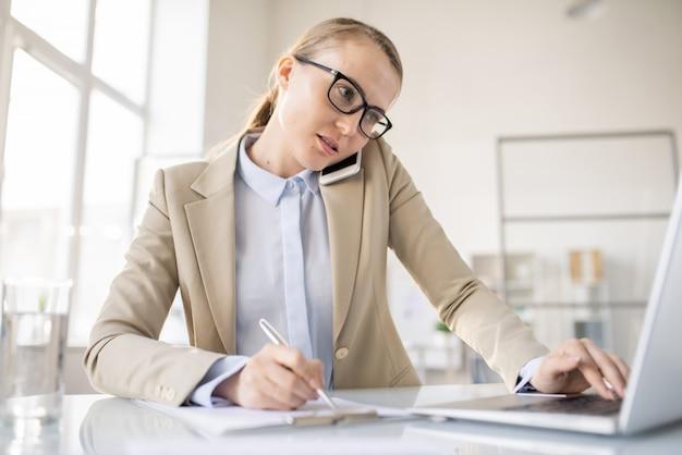 Jovem gerente ocupada em multitarefa falando ao telefone, usando laptop e fazendo anotações em papel no escritório, conceito trabalhador