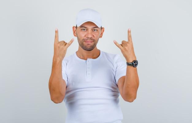 Jovem gesticulando com os dedos como rapper em camiseta branca, boné e olhando positiva, vista frontal.