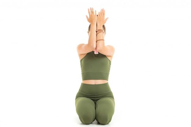 Jovem ginasta caucasiana com corpo atlético senta-se no chão com os olhos fechados, fazendo yoga e meditando isolado no fundo branco