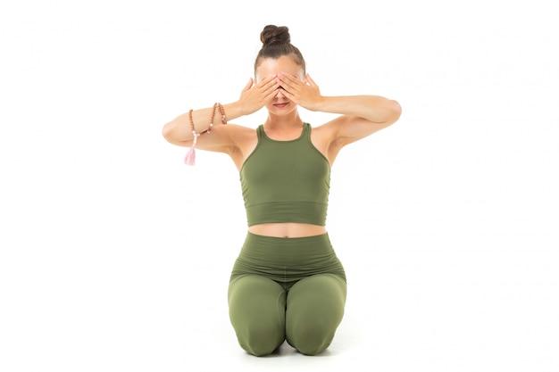 Jovem ginasta caucasiana com corpo atlético senta-se no chão com os olhos fechados, fazendo yoga e meditando