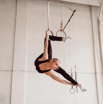 Jovem ginasta fazendo um exercício complicado
