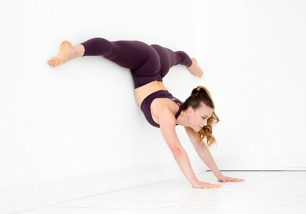 Jovem ginasta fazendo um pino dividir exercício de equilíbrio contra uma parede branca em um ginásio