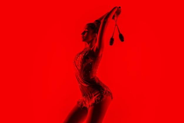 Jovem ginasta flexível isolada no vermelho