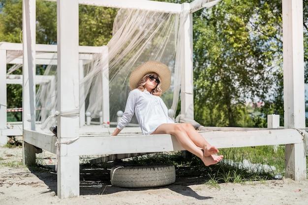Jovem glamorosa aproveita o estilo de vida e posa em um gazebo de madeira branco perto da praia do lago