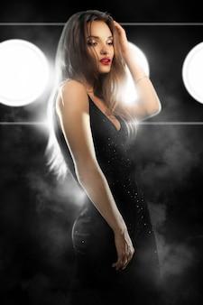 Jovem glamourosa com lábios vermelhos em um terno preto apertado olhando para o lado no estúdio na parede escura com fumaça e luzes