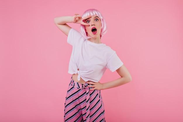 Jovem glamourosa em trajes da moda de verão usa peruca rosa. foto interna da modelo feminina positiva em uma camiseta branca relaxando durante a sessão de fotos